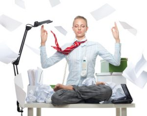 Calm business woman despite huge disorder on table and flying papers